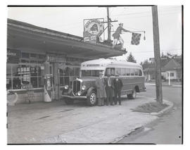 Three unidentified men with Milwaukie bus at Gilmore Oil station