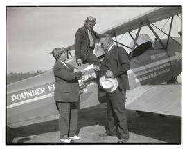 George L. Baker and two unidentified men with airplane