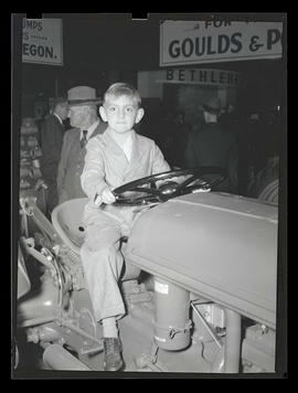 Unidentified boy on tractor, probably at Pacific International Livestock Exposition