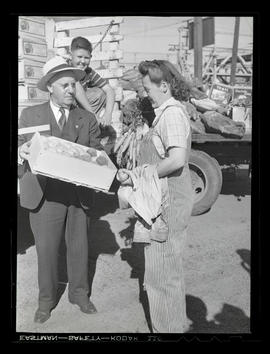 George Rodgers? and unidentified worker holding produce during market at Albina Engine & Mach...