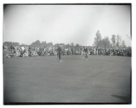 Crowd watching two golfers on green