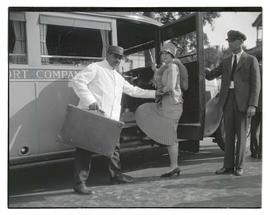 Helen Hawkins and two unidentified men with bus after christening ceremony