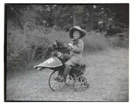 Costumed boy on tricycle decorated as horse
