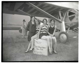 Four unidentified women posing with crate at airfield