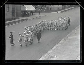 Prisoners and armed guards walking down street