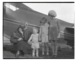 Woman and three children next to airplane
