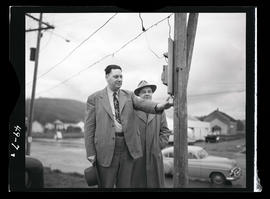 Unidentified men looking at utility pole