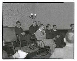 Unidentified men at meeting or hearing?