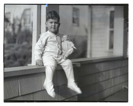 Unidentified young boy seated on railing and holding doll