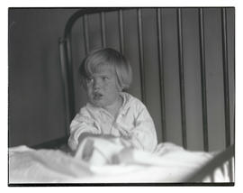 Unidentified young boy in bed