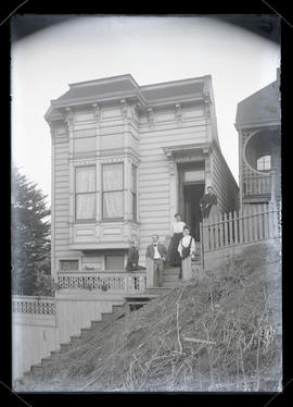 Group of unidentified people outside two-story house