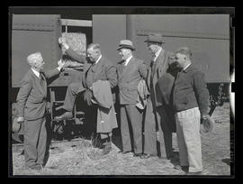 Five unidentified men next to train car, probably at Pacific International Livestock Exposition