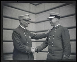 Portland Fire Chief Lee G. Holden shaking hands with fire marshal Edward Grenfell