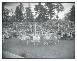 Girls performing maypole dance in park