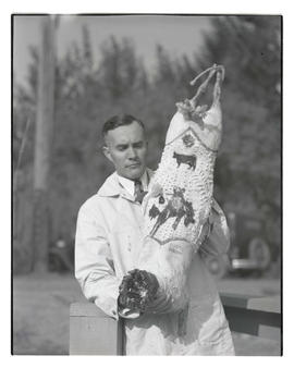 Unidentified man holding Swift's whole hog, probably at Pacific International Livestock Exposition
