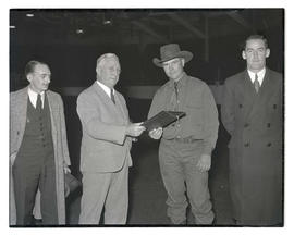 Man receiving plaque, possibly at livestock show