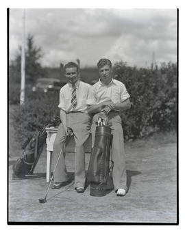 Two unidentified golfers posing with clubs