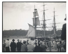 Crowd watching crew members set sails on USS Constitution's mizzenmast