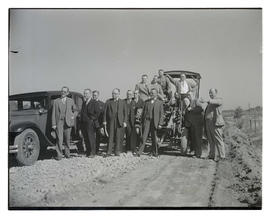 Group of men on dirt road with grader?