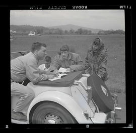 Four people with car at auto races in Tillamook, June 1955