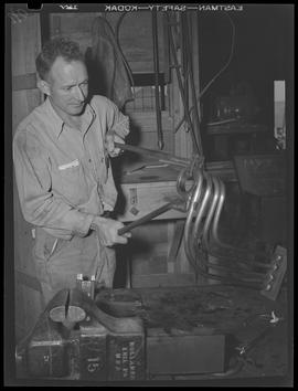 War industry worker bending metal tube at Albina Engine & Machine Works, Portland