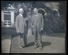 Unidentified man and Herbert Hoover on lawn outside building