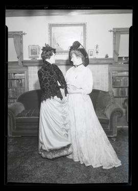 Two costumed women in sitting room