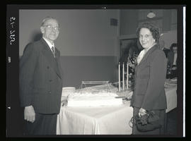 Two people standing next to table with decorative cake