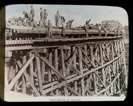 Railroad track being laid on trestle bridge