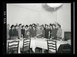 Group of women standing around table wearing hats