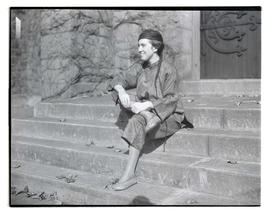 Unidentified woman in costume, sitting on steps outside stone building