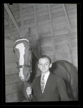 Boy and horse in stall