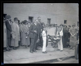 George L. Baker, two boys with flag, and crowd at unidentified ceremony