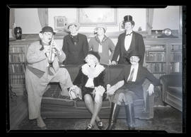 Six costumed people in sitting room
