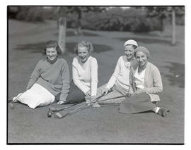 Four unidentified golfers sitting on golf course