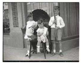 Three unidentified children posing with toys