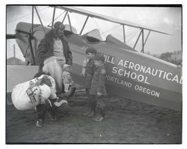 Two boys next to airplane with Santa Claus and pilot Gordon Mounce