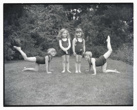 Four young girls in leotards or swimming suits, posing outdoors
