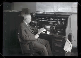 Unidentified man sitting at desk and reading letter
