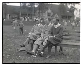 Three golfers seated on bench