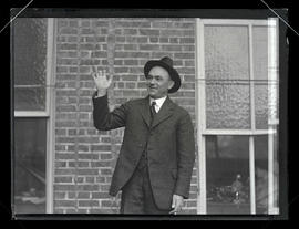 Unidentified man posing with hand raised