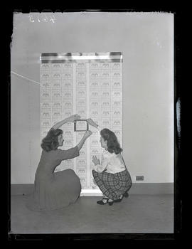 Two unidentified women with display of honor roll certificates for donations to United War Chest