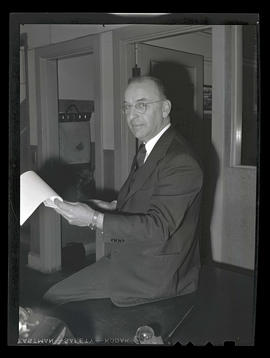 L. R. Hussa, vice president of Albina Engine & Machine Works, sitting on desk
