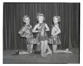 Three young tap dancers posing in costume