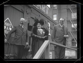 George L. Baker,  unidentified man, and unidentified woman on platform