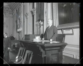 Gus C. Moser?, standing at president's seat in Oregon Senate chambers