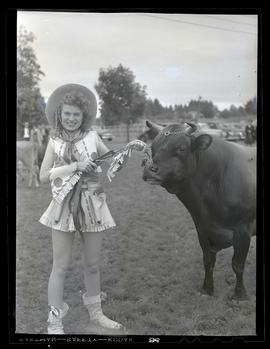 Costumed young woman standing with bull or steer