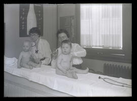 Two women examining babies during eugenics test?
