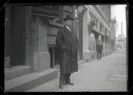 Unidentified man standing on sidewalk, full-length portrait