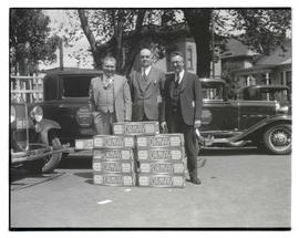 Three unidentified men posing with stacked boxes of Formay shortening